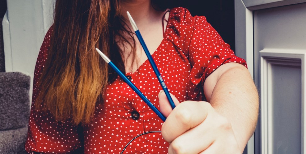 Girl holding blue knit pro knitting needles