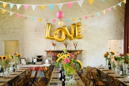 21 Jumbo Ideas for Gold Letter Balloons at Your Wedding     Colorful wedding with bunting  sun flowers and gold foil balloons  spelling LOVE