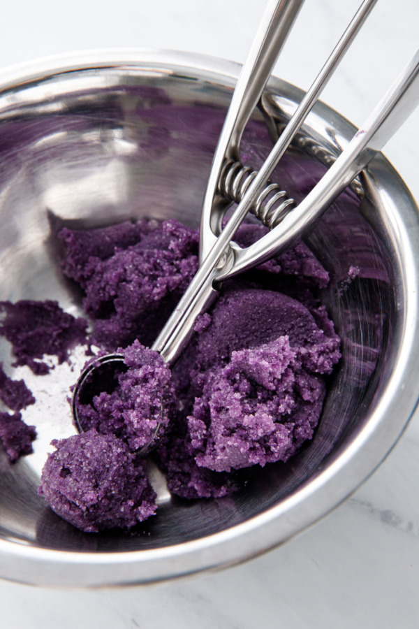 Silver mixing bowl with bright purple ube amaretti cookie dough and a metal cookie scoop