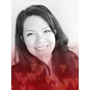 """Megan N smiles for a headshot with red hearts rising from the bottom of the frame. Search """"anxiety therapist near me"""" for support with online anxiety therapy in Sacramento, CA, anxiety treatment in Sacramento, CA, and other services."""