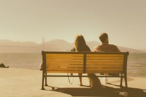A couple sits on a bench overlooking a vast lake. Contact a online couples therapist in Sacramento, CA for support with online couples sex therapy in California and other services.