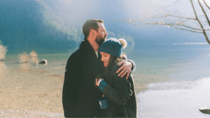 A couple embraces in front of a large lake surrounded by trees. Online couples therapy and marriage counseling in California can help relationships thrive. Contact a Sacramento therapist for support with online anxiety therapy, online lgbt therapy, and other services.