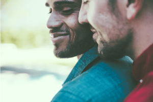 A happy gay couple smile with one another. Contact a sacramento therapsit for support with online lgbt therapy in california and other services.