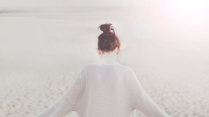 A lone woman stands overlooking endless sand. This could represent the isolation of anxiety. Contact an anxiety therapist in sacramento, ca for online anxiety therapy and other services.
