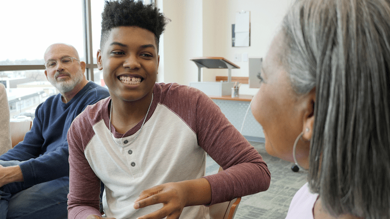A black teen smiles as they share something with the woman sitting next to them in the group they are part of. This could represent what therapy for teens in Sacramento, CA may look like. We offer support for teens and their families through online therapy for teens in California. Contact a therapist for teens today for support!