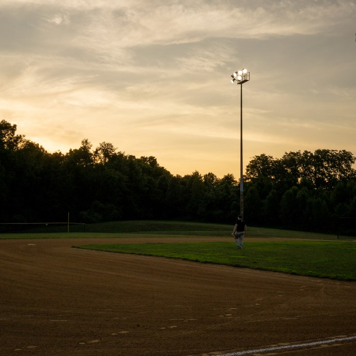 A 16u baseball player walks to his position during a Wednesday night pick-up game on July 29, 2020 in Loveland, Ohio.