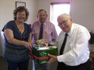 Director of Nursing Mrs. Alicia Trimingham-Turl receives the Gift Hamper from Mr. Bob Sellers and Mr. Jim Tyrell for the Order of St Johns