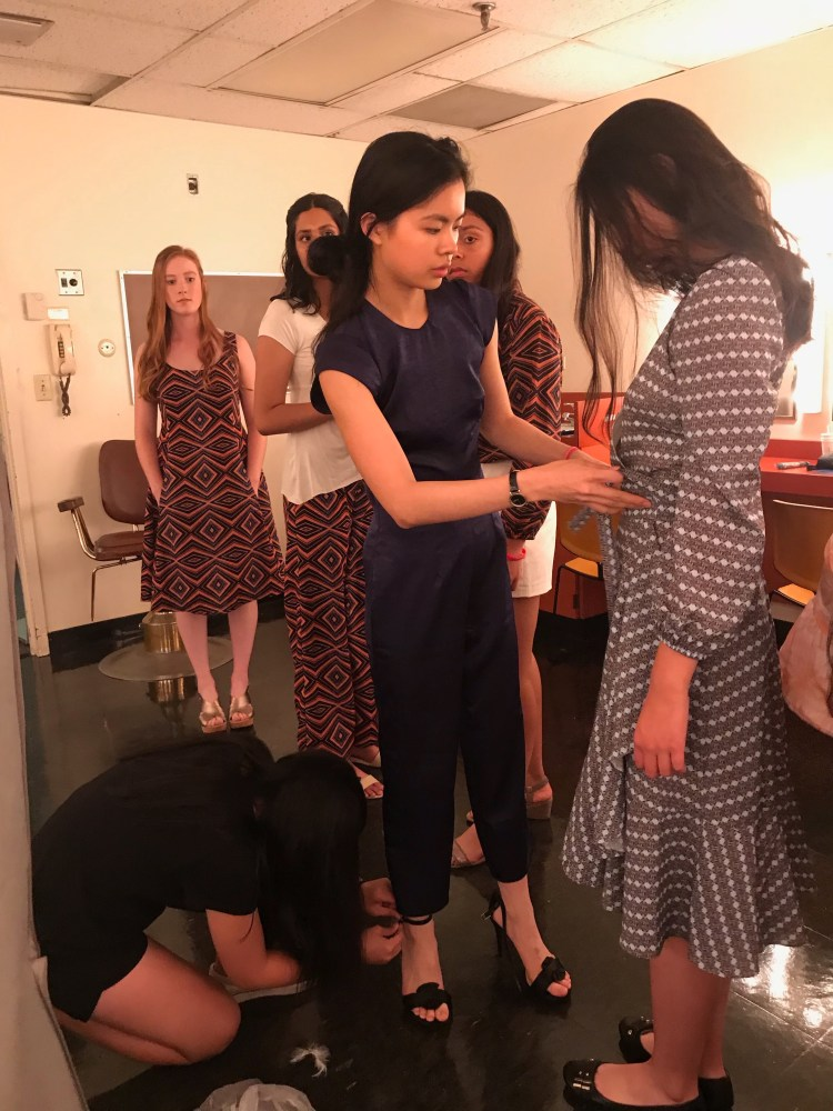 My sister who is the sweetest, helping me change heels while I adjust models' clothing.