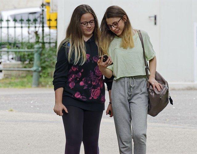 Girls-watching-mobile-walking-(lovestatuswhatsapp.com)