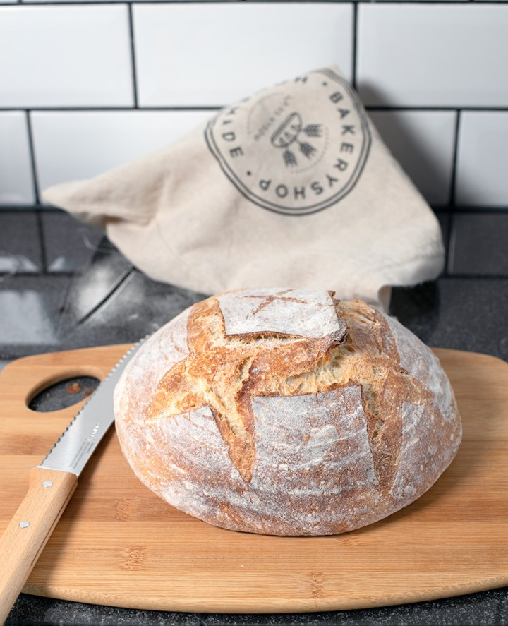 Sourdough loaf on cutting board with Opinel bread knife
