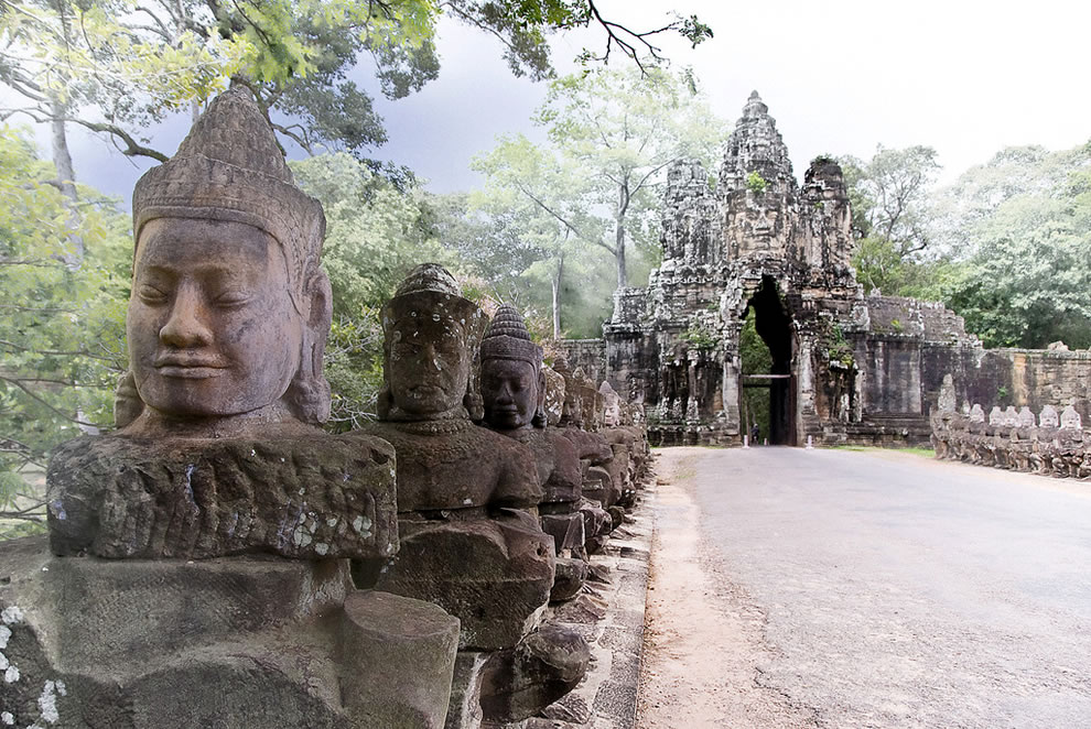 Mythic statues line the causeway over a moat leading to the south gate of Angkor Thom