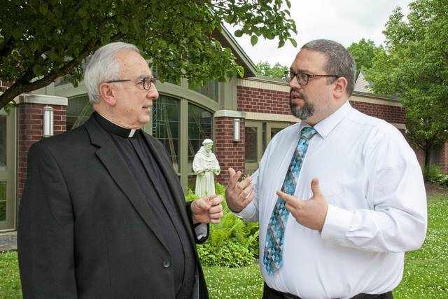 Mark Dunmire (right) talks with Monsignor James T. Gaston, pastor of Mother of Sorrows Parish, Murrysville.