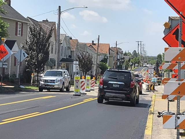 Two-way traffic passes through narrow 11-foot lanes on Latrobe's Lloyd Avenue on Friday, June 28, 2019, as a PennDOT contractor prepares to replace a bridge with a box culvert.