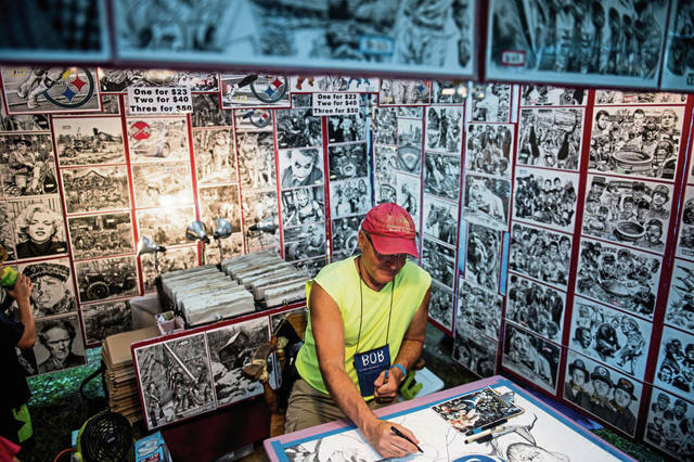 Artist Bob Weaver of West Newton works on a pen-and-ink drawing of Penn State wrestling during the Westmoreland Arts and Heritage Festival at Twin Lakes Park east of Greensburg on Friday<ins>, July 5, 2019</ins>.