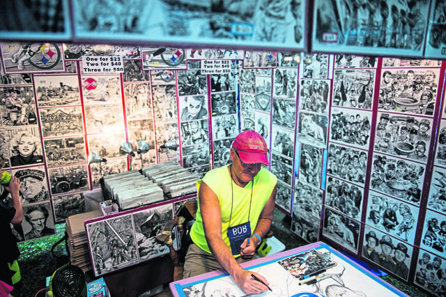 Artist Bob Weaver, of West Newton, works on a pen and ink drawing of Penn State wrestling, during the Westmoreland Arts and Heritage Festival at Twin Lakes Park in Unity Township, on Friday, July 5, 2019.