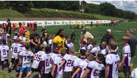 Plum Midget Football Association players high-five Steelers players as they made their way onto the practice field at St. Vincent College on Friday<ins>, July 26, 2019</ins>.