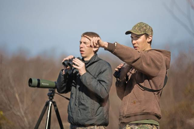From left, Fayette County brothers Calvin Livengood and Peter Livengood, who are students at California University of Pennsylvania, watch for birds of prey on a section of Chestnut Ridge in Dunbar Township, Fayette County.