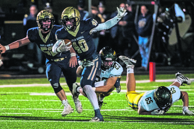 Franklin Regional's Zac Gordon tries to gain yardage as Penn- Trafford defender Chase Burk grabs a tackle during WPIAL football on Friday, Oct. 25, 2019.