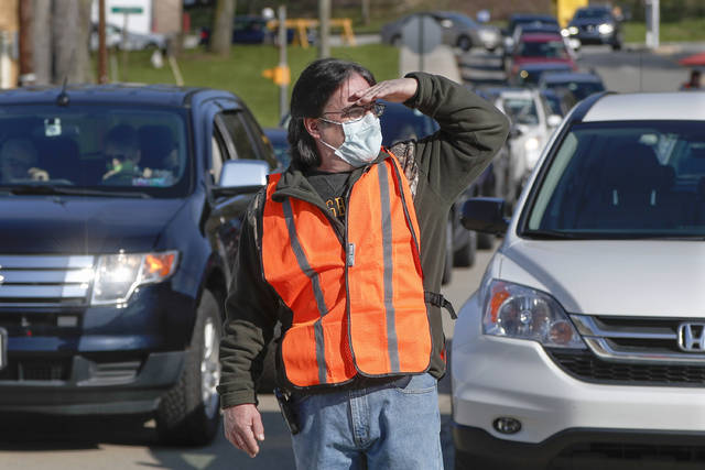 A volunteer wearing a protective mask, looks to direct the cars lined up to make purchases from their cars at the Greensburg Farmers' Market opening day, Saturday, April 25, 2020, in Greensburg .