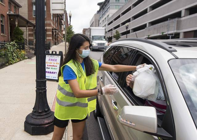 Sabrina Pettinato helps hand out free grab-and-go meals for families with kids outside Otterbein United Methodist Church in Greensburg on July 23, 2020.