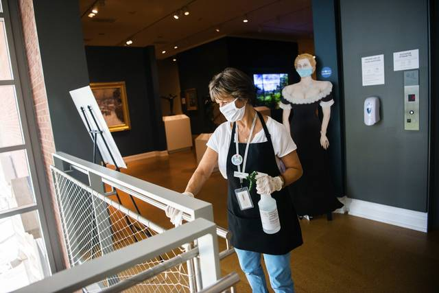 Westmoreland Museum of American Art gallery host Sharon Ferencz disinfects the handrails at the stairwell Wednesday as the Greensburg museum reopened to the public.
