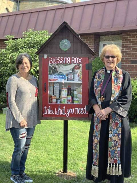 "Tricia Lowden (left) and the Rev. Shirley Musick pose with Trinity United Church of Christ's ""Blessing Box"" in Greensburg."