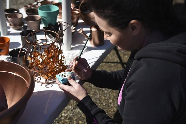 Tracy Bender of Greensburg personalizes a ceramic owl for a customer at her booth at the Irwin Fall Festival at the Banco Business Park on Saturday<ins>,</ins><ins> Oct. 17, </ins><ins>2020</ins>.