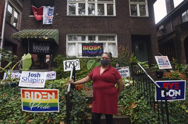 Tracy Baton stands among pro-Biden signs outside her home in Pittsburgh's Point Breeze neighborhood.