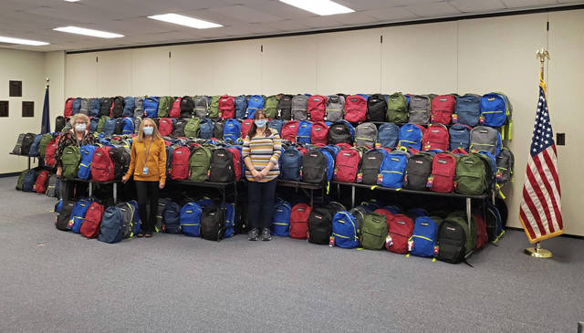 Employees at the Westmoreland Intermediate Unit (from left) Christie Ridenour, Kathy Dull and Dee Petrie stand in front of 1,000 backpacks stuffed with items donated by community groups to benefit homeless students around Western Pennsylvania.