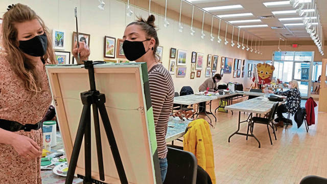 Instructor Sarah Hunter (left) of Greensburg helps Meah Ezykowsky of Latrobe with an acrylic painting.