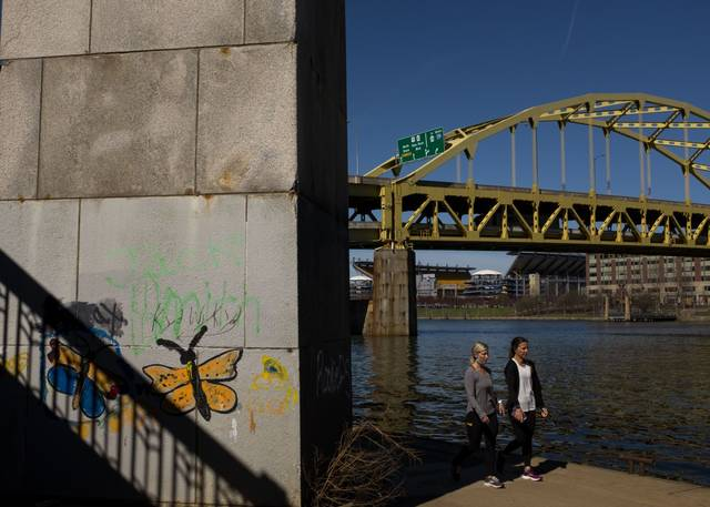People walk along the Allegheny River in Downtown Pittsburgh on March 30, 2021.