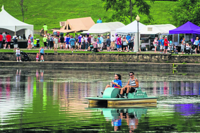 Festival-goers browse vendor booths and enjoy pedal boats during the 2019 Westmoreland Arts & Heritage Festival at Twin Lakes Park.