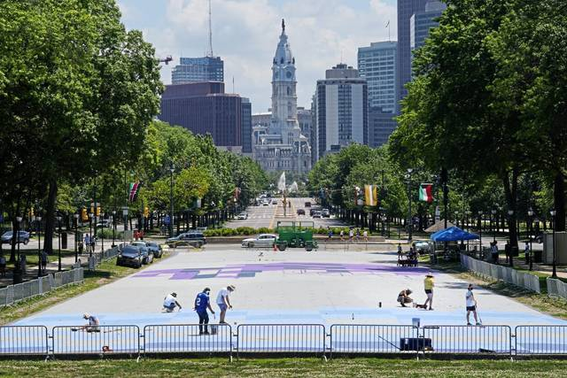 Mural Arts Philadelphia artists paint on the ground at Eakins Oval in Philadelphia, Monday, June 28, 2021.