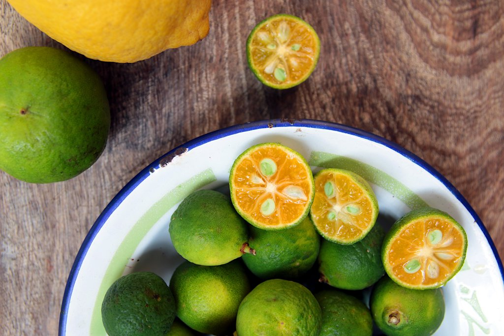 Limes, Calamansi and Lemons on a wooden board