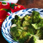 stir fried broccoli florets with garlic placed on a blue and white ceramic bowl