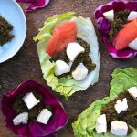 Italian tapenade spread on red and green cabbage leaves, sprinkled with feta cubes, mozzaralla and salmon, served on a wooden tray