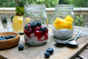 Two glass jars with creamy coconut milk, topped with berries and pineapple, and two spoons
