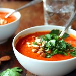 two white bowls with spicy tomato soup with red pepper, topped with parsley leaves and chopped almonds