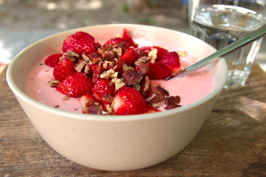 A bowl of strawberry yogurt topped with strawberry halves and chopped pecan nuts