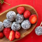 chocolate coconut balls served with strawberries in a wooden bowl, placed on a red table