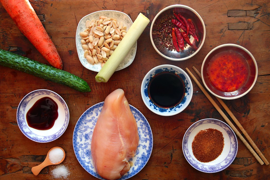 ingredients for Kung Pao chicken spread on a wooden board in small bowls or plates: chicken breast, carrot, cucumber, leek, peanuts and Sichuan peppercorns