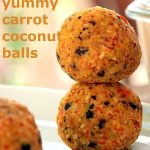 Two carrot coconut balls atop each other on a white place with sunlight coming in from behind