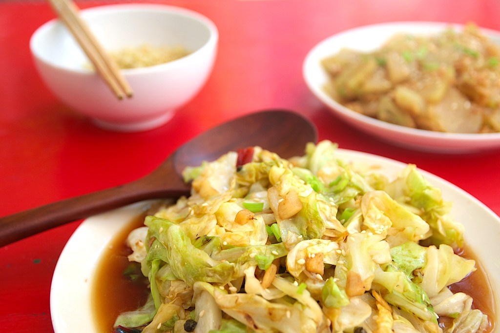 a white plate with stir fried cabbage on a red table