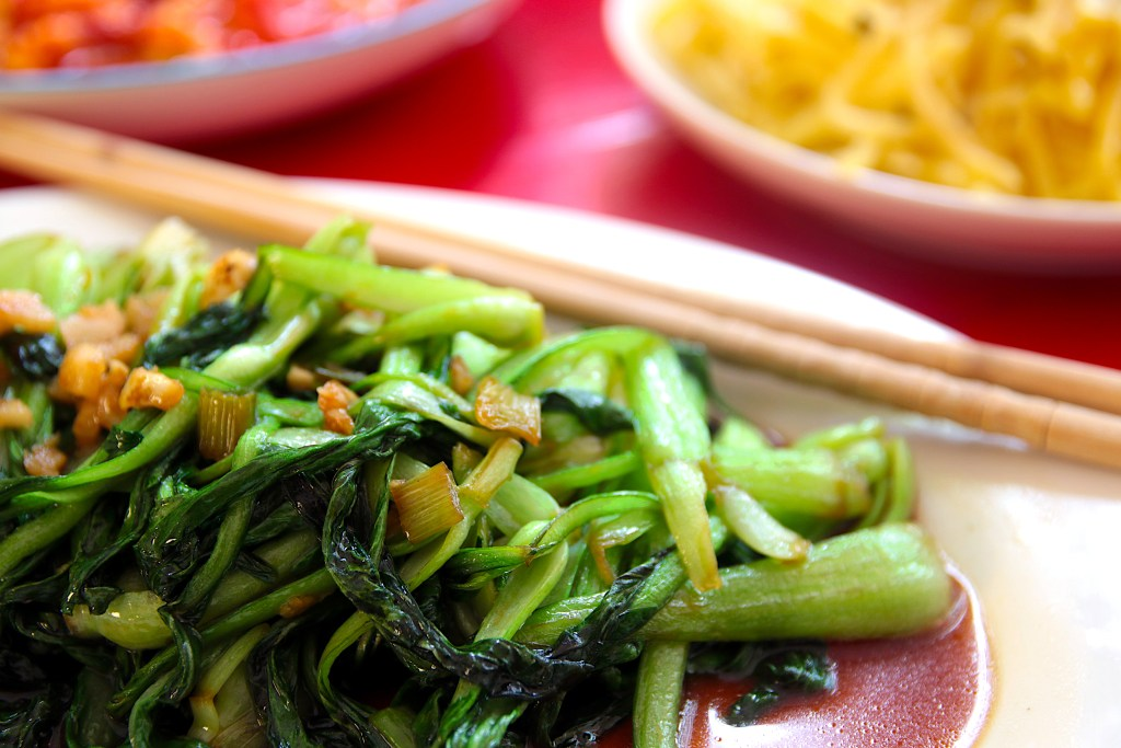 a white serving plate with stir fried bok choy with chopsticks, with other dishes in the background