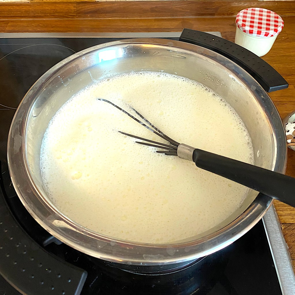 milk and a whisk in a pot on a stove for heating