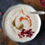 A bowl with raita yogourt dip sprinkled with pomegranate seeds on a wooden table