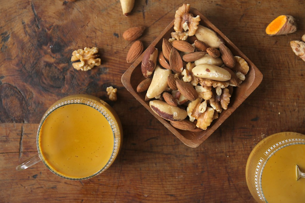 Two cups of golden milk on a wooden table, viewed from above and served with a few nuts