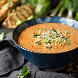 Peanut sauce garnished with cayenne pepper, cilantro, green onion and crushed peanuts in a blue Asian print bowl placed on a dark gray napkin with chicken satay on skewers, scallions and peanuts in the background.