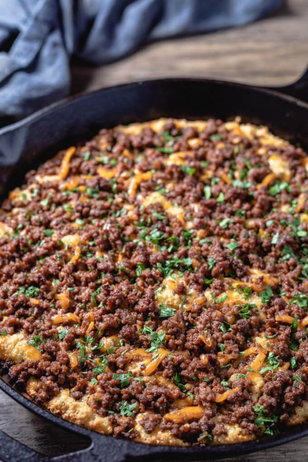 Sloppy Joe casserole with cheese in a cast iron skillet.