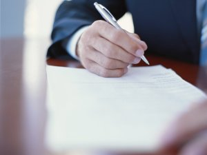 Businessman writing at desk, close-up Lowell Social Security Disability Attorney